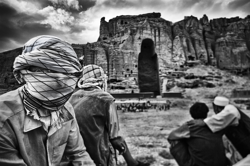 Afghan men gather in front of the remains of the statue of the big Buddha.