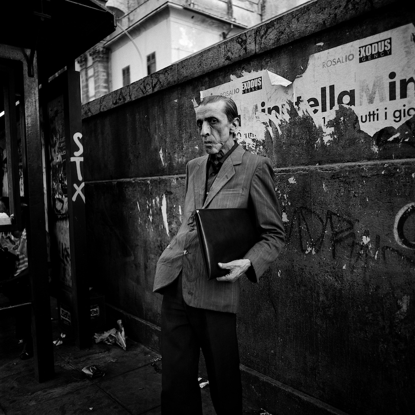 A man is waiting for the bus at a vandalised bus top inb Palermo. March 2009
