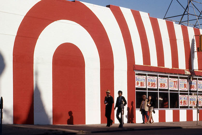 red_and_white_striped_storefront_with_passersby_attrib_to_arthur_stross_around_1970